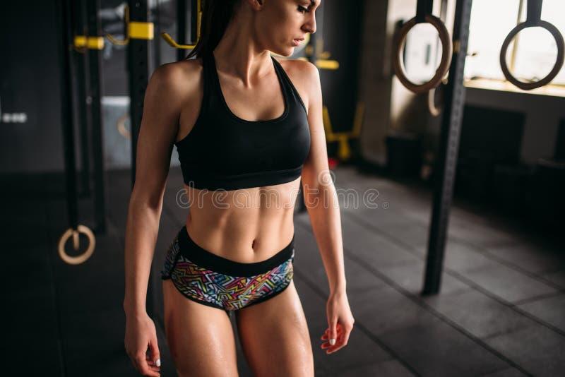 Atleta de sexo femenino con el cuerpo muscular que presenta en gimnasio fotografía de archivo
