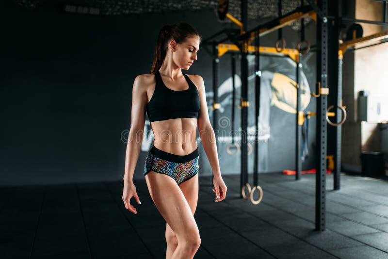 Atleta de sexo femenino con el cuerpo muscular que presenta en gimnasio fotografía de archivo libre de regalías