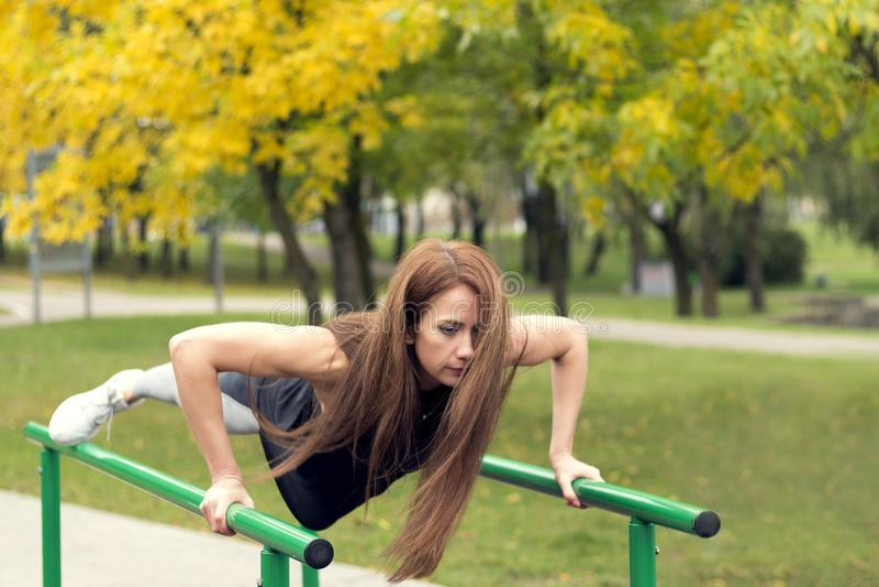 Atleta de sexo femenino hermoso que ejercita en las barrases paralelas, haciendo pectorales imagen de archivo