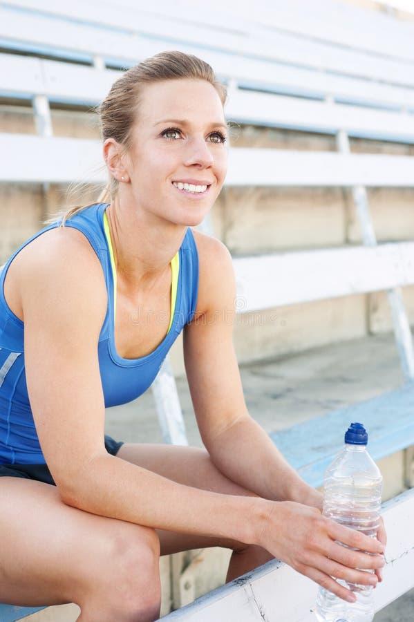 Atleta de sexo femenino joven con la botella de agua foto de archivo libre de regalías