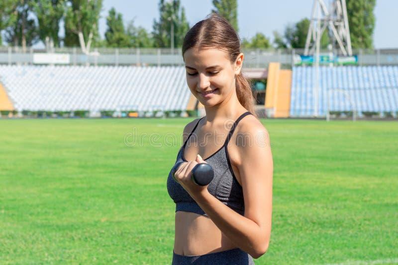 Atleta de sexo femenino joven con las pesas de gimnasia que estiran y que calientan en pista corrida en deporte del estadio y con imágenes de archivo libres de regalías