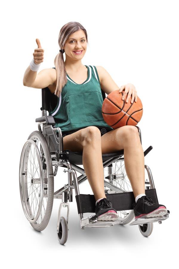 Atleta de sexo femenino joven en una silla de ruedas que lleva a cabo baloncesto y que muestra los pulgares para arriba fotografía de archivo libre de regalías