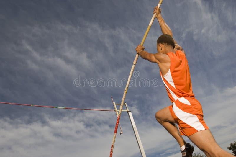 Atleta de sexo femenino Performing un salto con pértiga fotografía de archivo libre de regalías