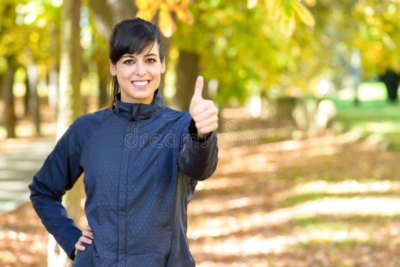 Atleta de sexo femenino positivo con los pulgares para arriba