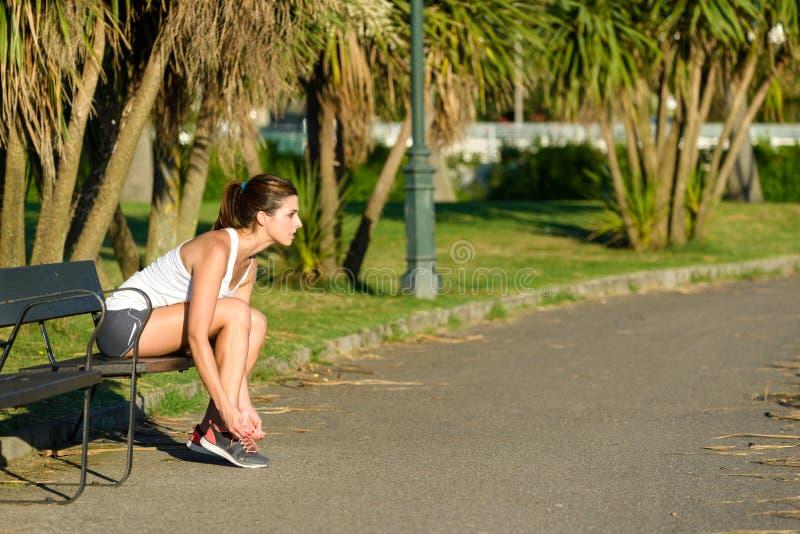 Atleta de sexo femenino que ata los cordones de zapatos del deporte para correr fotografía de archivo libre de regalías