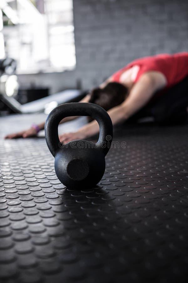 Atleta de sexo femenino que ejercita por el kettlebell fotografía de archivo