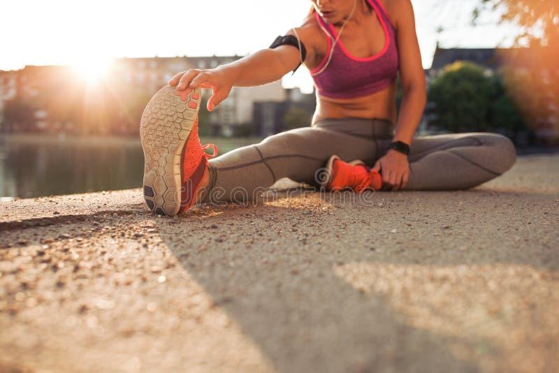 Atleta de sexo femenino que estira las piernas imagenes de archivo