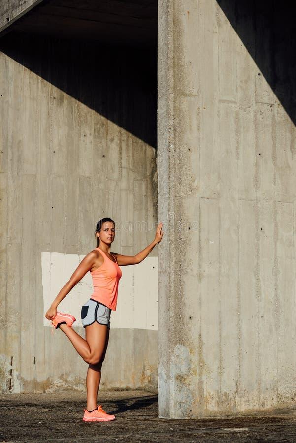 Atleta de sexo femenino que estira las piernas para correr imagenes de archivo