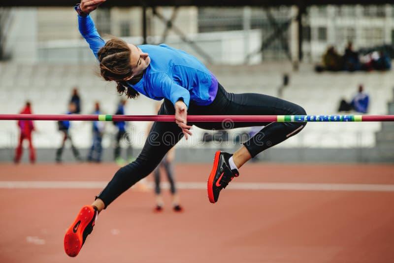 atleta de sexo femenino que salta tentativa acertada en el salto de altura fotos de archivo