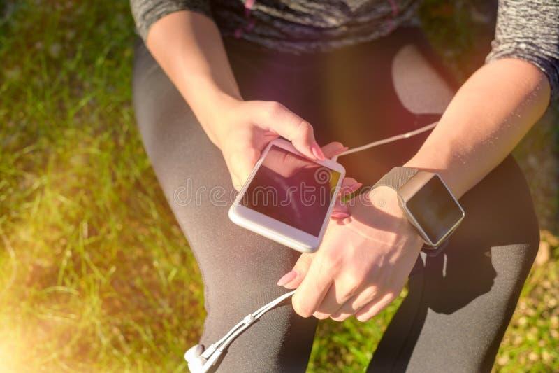 Atleta de sexo femenino que usa la aptitud app en su reloj elegante para supervisar funcionamiento del entrenamiento Concepto usa foto de archivo libre de regalías