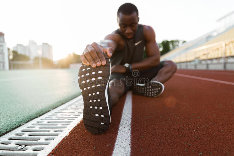 Atleta de sexo masculino africano concentrado jóvenes que estira las piernas imagenes de archivo