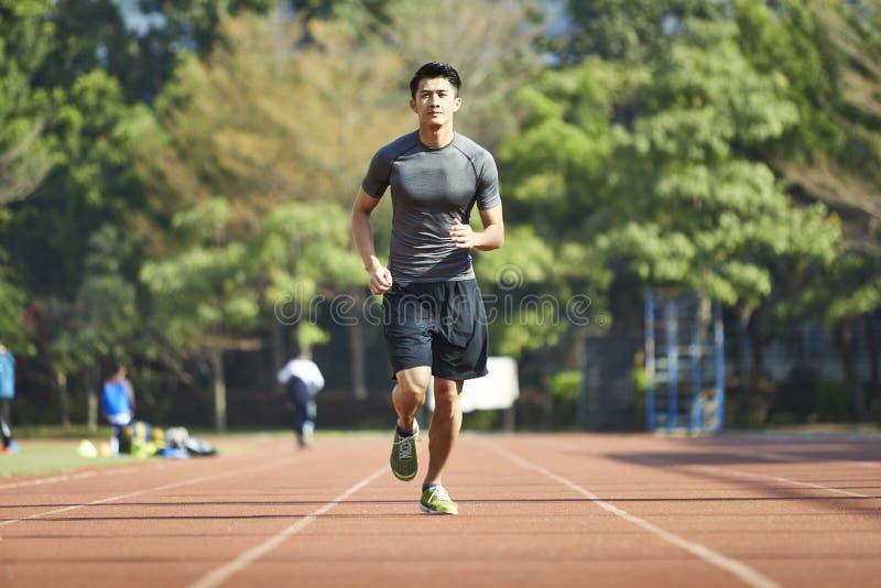 Atleta de sexo masculino asiático joven que corre en pista imágenes de archivo libres de regalías