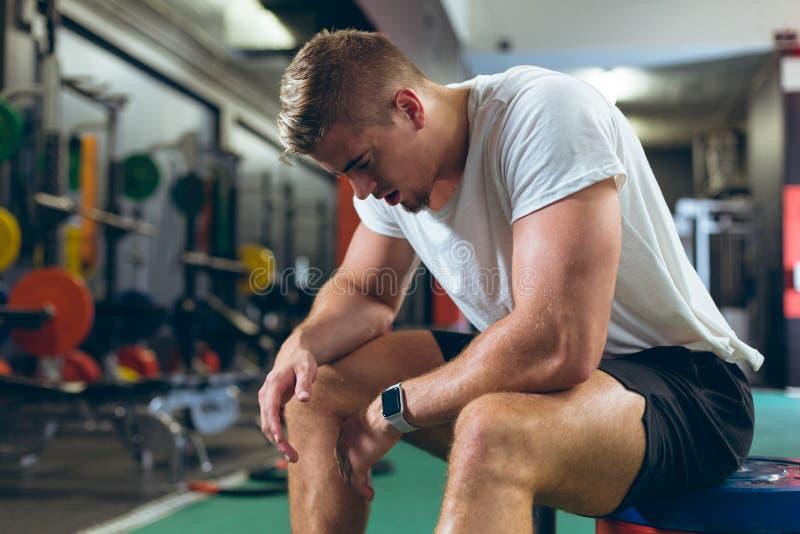 Atleta de sexo masculino cansado que se sienta en centro de aptitud foto de archivo libre de regalías