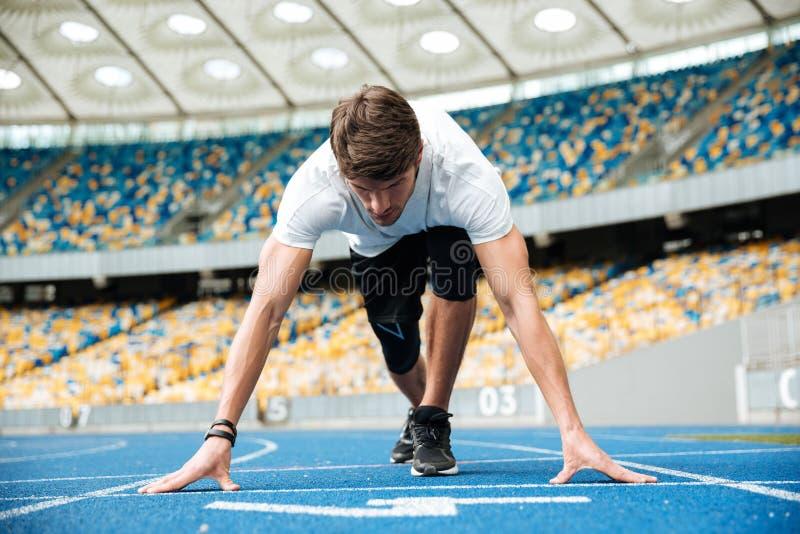 Atleta de sexo masculino confiado que se coloca en la posición de salida lista para correr imagen de archivo libre de regalías
