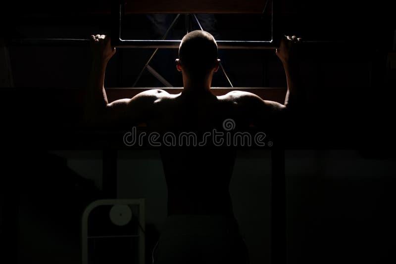 Atleta de sexo masculino Doing Pull Ups del levantamiento de pesas de Siluet fotos de archivo libres de regalías