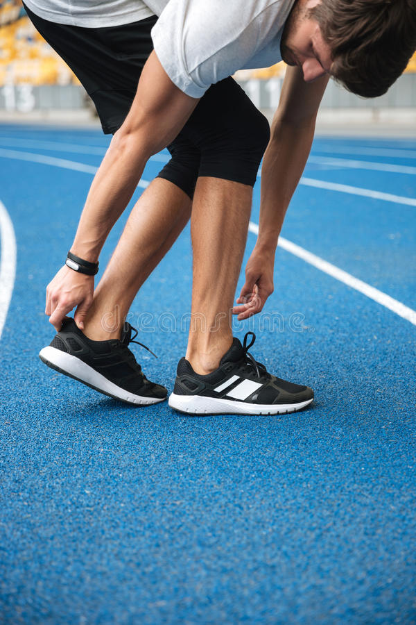 Atleta de sexo masculino en ropa de deportes que calienta antes de correr imagen de archivo