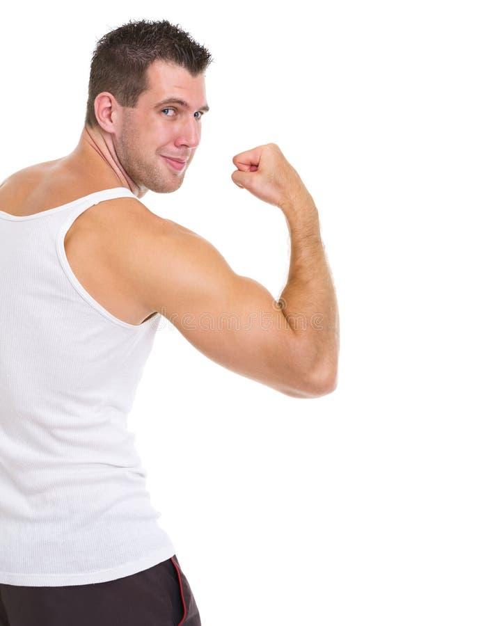 Atleta de sexo masculino feliz que muestra el bíceps fotos de archivo