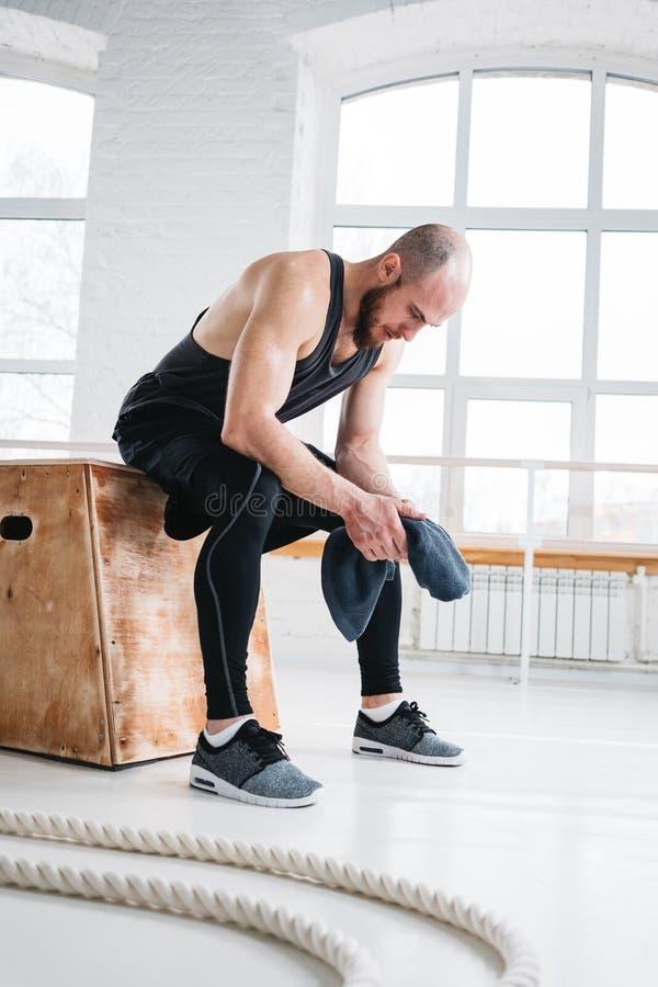 Atleta de sexo masculino fuerte que descansa después de entrenamiento duro imagen de archivo