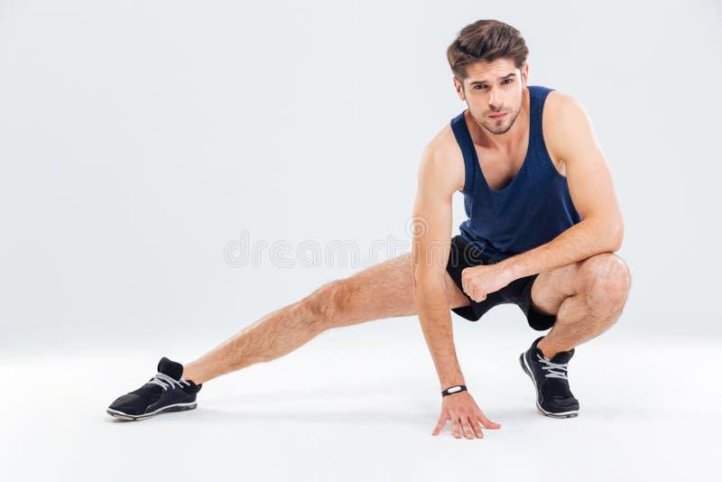 Atleta de sexo masculino joven atractivo que estira sus piernas imágenes de archivo libres de regalías