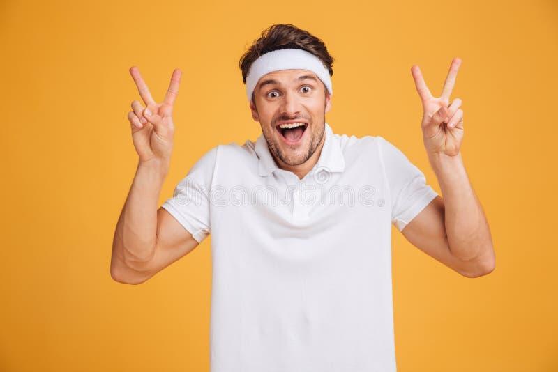 Atleta de sexo masculino joven emocionado feliz que grita y que muestra la muestra de la victoria imágenes de archivo libres de regalías
