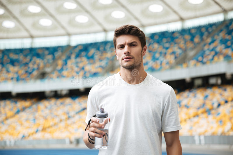 Atleta de sexo masculino joven que sostiene la botella de agua imagen de archivo libre de regalías