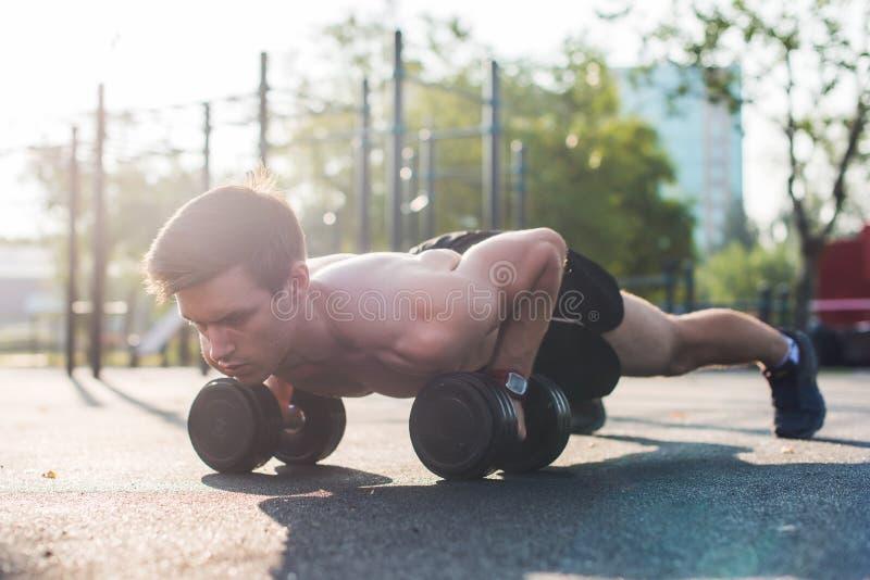 Atleta de sexo masculino muscular que hace ejercicios de los pectorales fotos de archivo