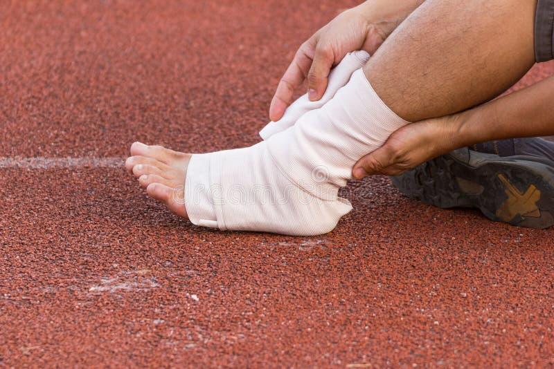 Atleta de sexo masculino que aplica el vendaje de compresión sobre herida en el tobillo de un futbolista, foto de archivo libre de regalías