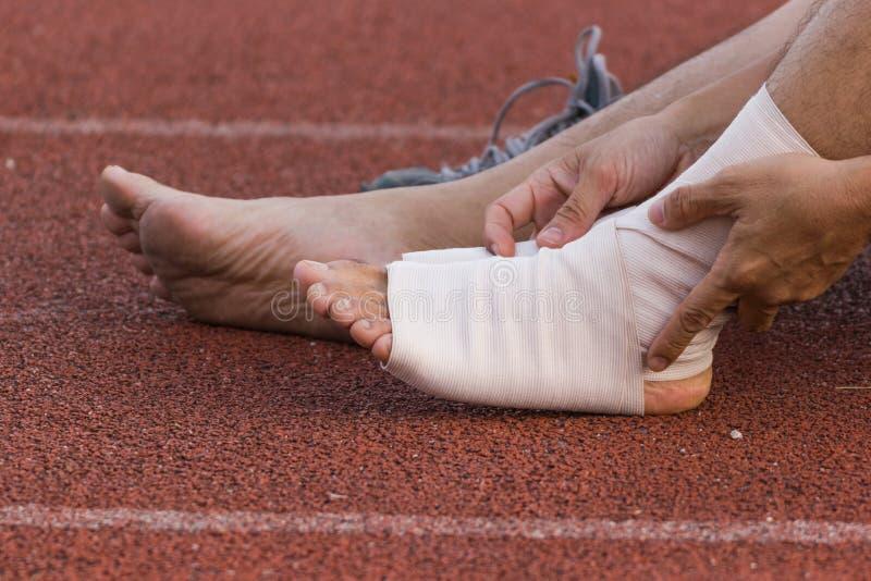 Atleta de sexo masculino que aplica el vendaje de compresión sobre herida en el tobillo de un futbolista foto de archivo