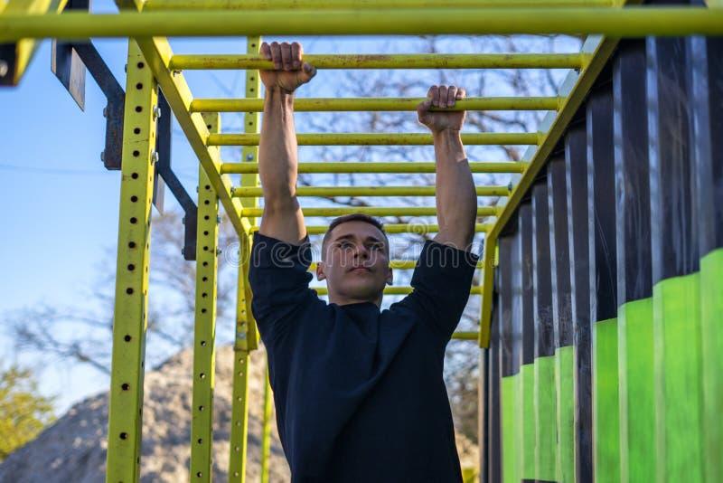 Atleta de sexo masculino que balancea en barras de mono imágenes de archivo libres de regalías