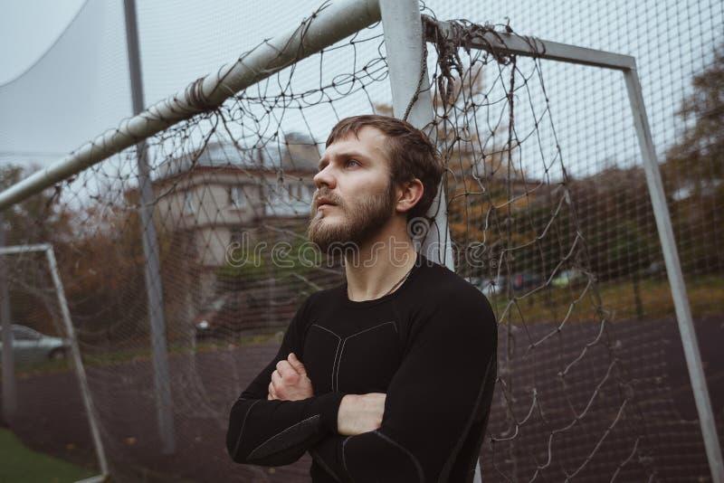 Atleta de sexo masculino que descansa sobre campo de fútbol fotografía de archivo libre de regalías