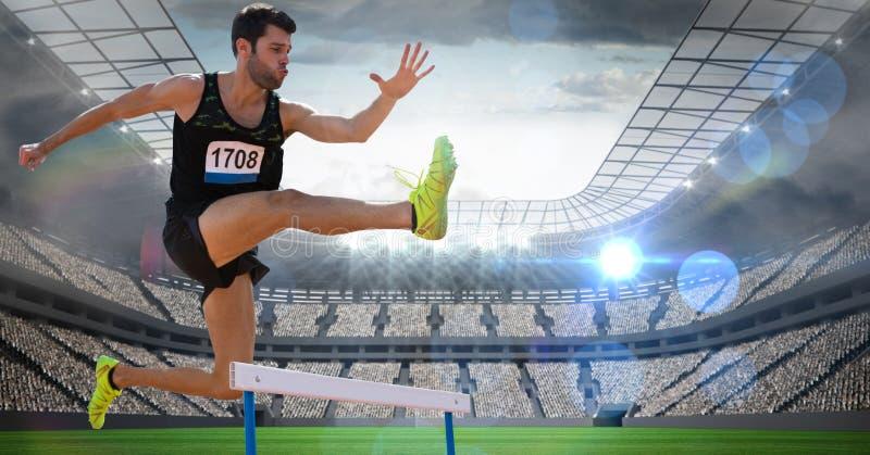 Atleta de sexo masculino que salta sobre el obstáculo en estadio imagen de archivo