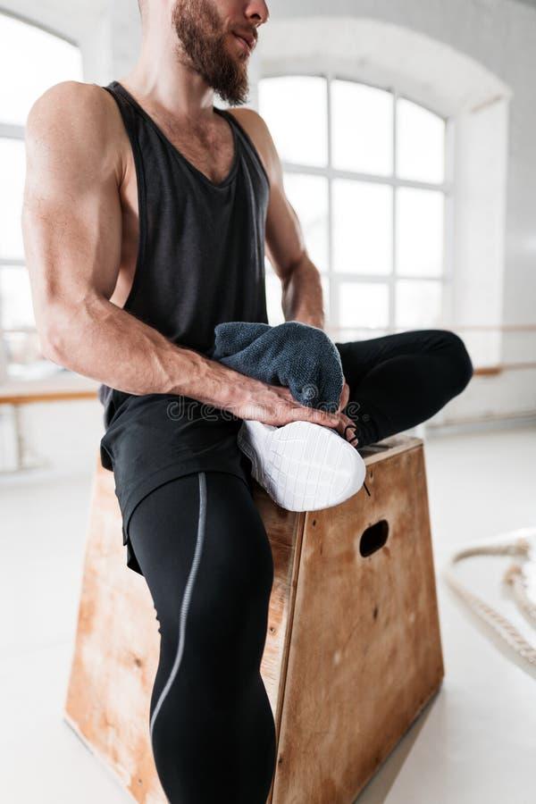 Atleta de sexo masculino de transpiración que descansa después de entrenamiento duro del crossfit en gimnasio ligero imagen de archivo libre de regalías