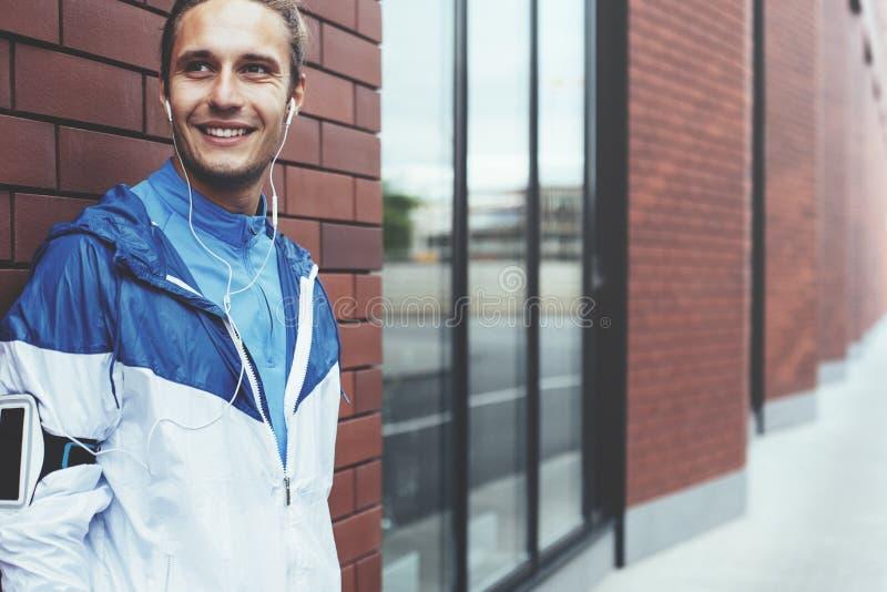 Atleta de sorriso na posição azul na rua e na preparação para movimentar-se imagens de stock royalty free