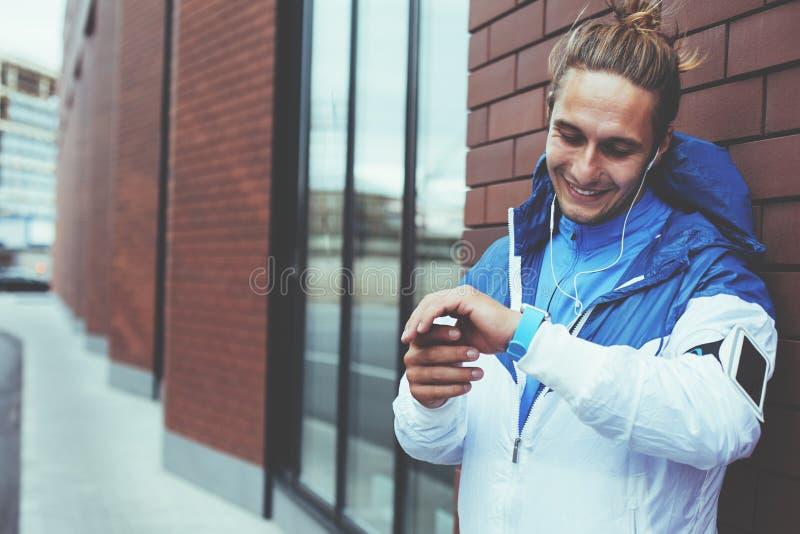 Atleta de sorriso na posição azul na rua e na preparação para movimentar-se, ajustando o programa do exercício em seu relógio esp imagens de stock royalty free