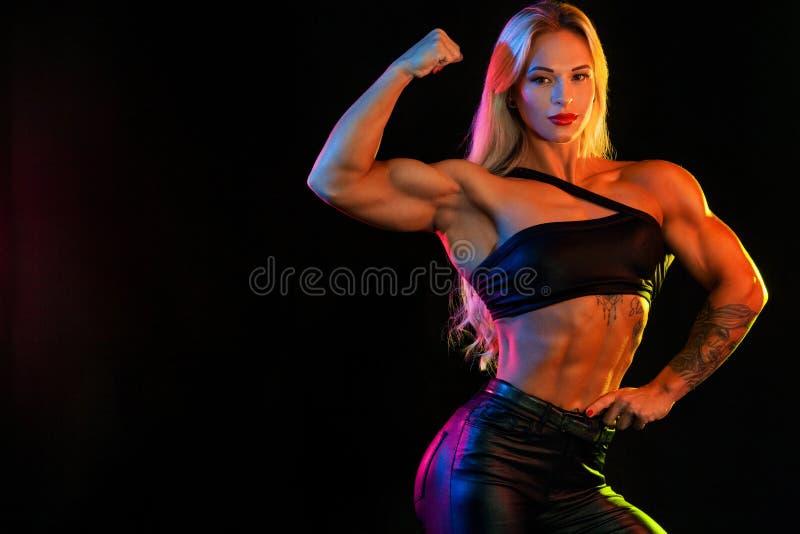 Atleta del campione del culturista della donna, su fondo nero fotografia stock