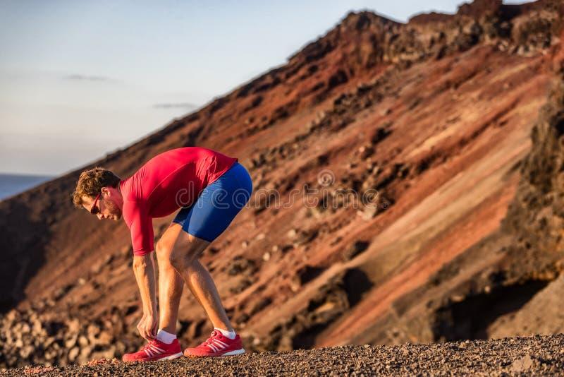 Atleta del corredor que consigue listo para entrenar al ejercicio cardiio que ata el cordón de zapatillas deportivas que se prepa imágenes de archivo libres de regalías