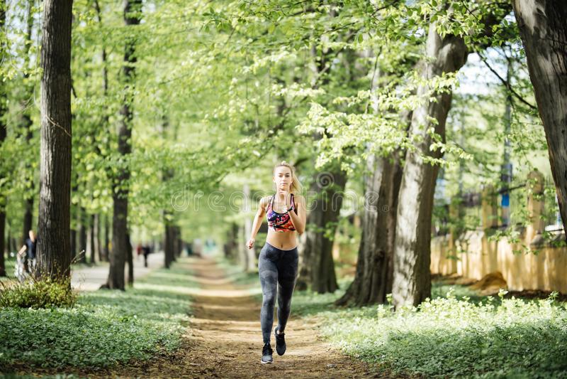 Atleta del corredor que corre en el parque del cityl Concepto de la salud del entrenamiento de la aptitud de la mujer que activa  foto de archivo