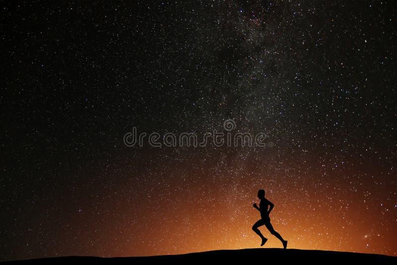Atleta del corredor que corre en la colina con noche estrellada hermosa imagenes de archivo
