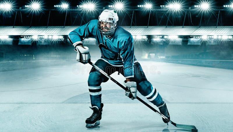 Atleta del giocatore di hockey su ghiaccio nel casco e guanti sullo stadio con il bastone Colpo di azione Concetto di sport immagine stock