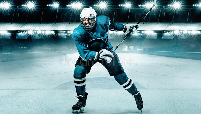 Atleta del giocatore di hockey su ghiaccio nel casco e guanti sullo stadio con il bastone Colpo di azione Concetto di sport immagine stock libera da diritti
