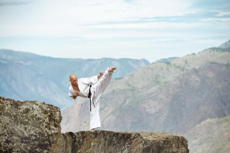 Atleta del karate que demuestra retroceso en el acantilado de las montañas imagen de archivo