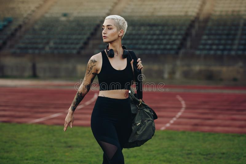Atleta della donna che cammina dentro uno stadio di atletica fotografia stock