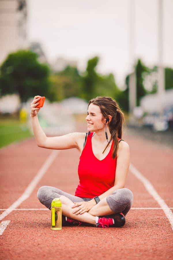 Atleta della giovane donna allo stile di vita di sport dello stadio, sedendosi sulla pista, prendente la foto del selfie su uno s immagine stock