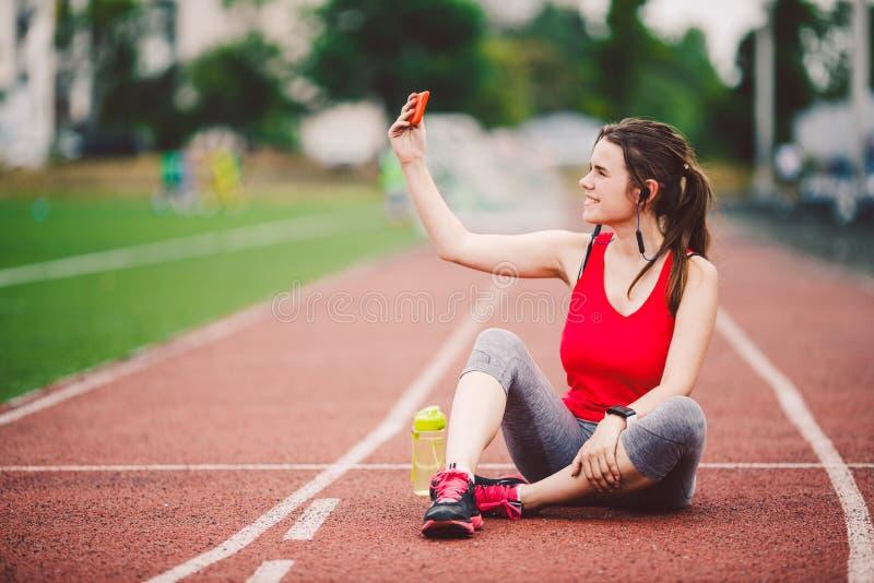 Atleta della giovane donna allo stile di vita di sport dello stadio, sedendosi sulla pista, prendente la foto del selfie su uno s immagini stock