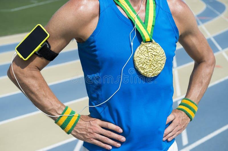 Atleta della medaglia d'oro con il bracciale del telefono cellulare immagine stock libera da diritti