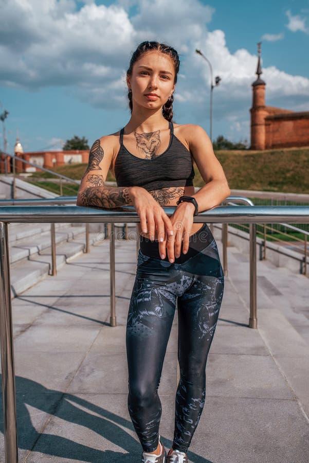Atleta della ragazza, città di estate Posando contro lo sfondo dei punti In scarpe da tennis delle ghette Donna con i tatuaggi si immagini stock libere da diritti