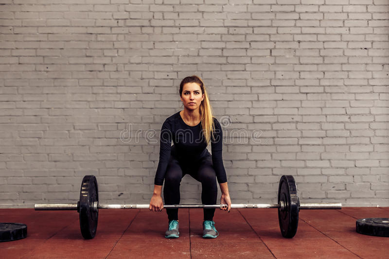 Atleta della ragazza nel deadlift di posizione di partenza immagine stock libera da diritti