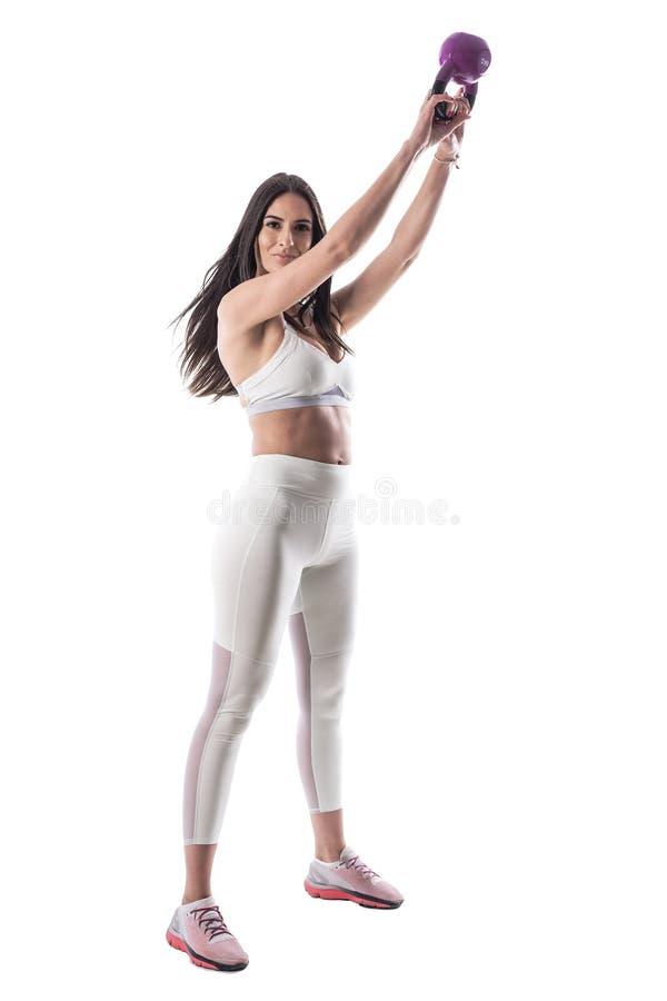Atleta della sportiva di forma fisica che fa sollevamento pesi del kettlebell che esamina macchina fotografica fotografia stock libera da diritti