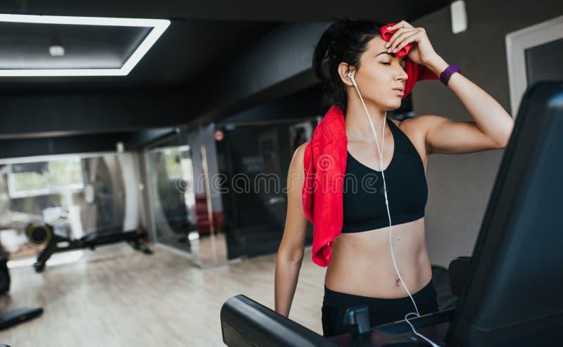 Atleta deportivo de la mujer joven que corre en la rueda de ardilla en el gimnasio, limpiado apagado con una toalla roja y escuch imagen de archivo libre de regalías