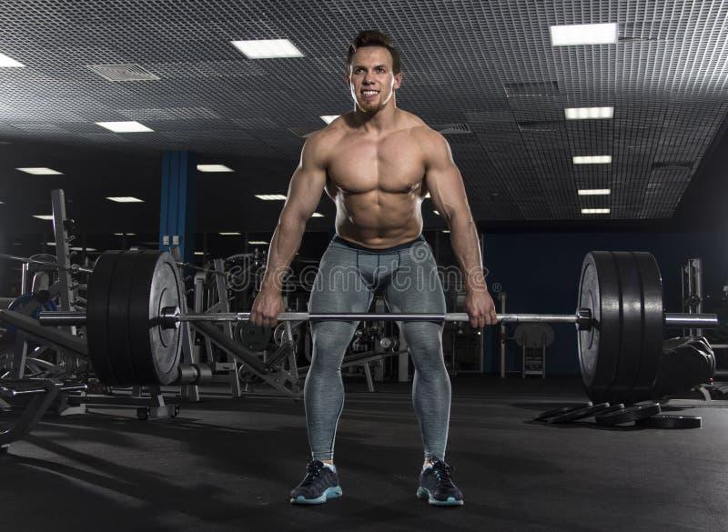 Atleta descamisado muscular atractivo que hace ejercicio pesado del deadlift imágenes de archivo libres de regalías